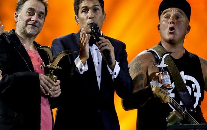 Chilean TV presenter Rafael Araneda stands between vocalist Vicentico, left, and bassist Sr. Flavio, of the Argentina rock band Los Fabulosos Cadillacs, who receive the seagull of silver and gold award at the Vina del Mar International Song Festival in Viña del Mar, Chile, Monday, Feb. 20, 2017. Believed to be one of the largest musical events in Latin America, the annual five-day festival was inaugurated in 1960. (AP Photo/Esteban Felix) Chile Vina del Mar Song Festival